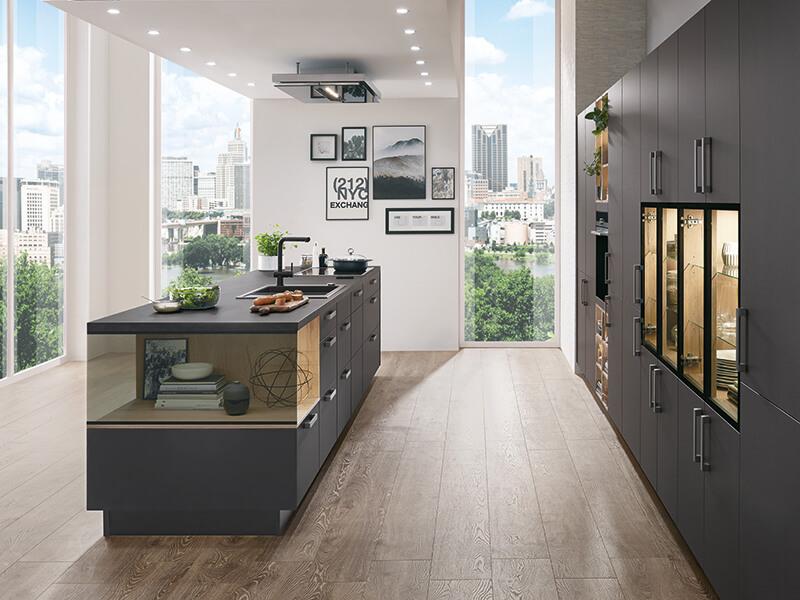 schwarze Kücheninsel mit Glas und Hochschrank mit Elektrogeräte und Spüle